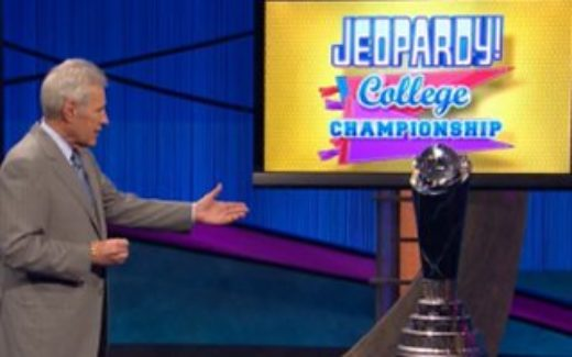 Alex Trebek shows off the College Championship trophy